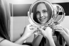 Woman in bathroom. Portrait of a beautiful freckles woman in the mirror. Black and white stock image