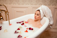 Woman in bathroom with rose petals Stock Photos
