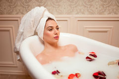 Woman in bathroom with rose petals Royalty Free Stock Photography