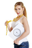 Woman with bathroom scale and measuring tape. Gesturing OK, isolated on white stock image