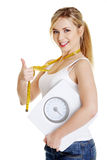 Woman with bathroom scale and measuring tape Royalty Free Stock Photo