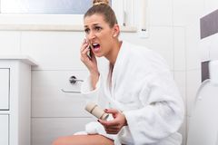 Woman on toilet complaining via phone about lack of paper Stock Photos
