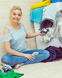 Woman wash laundry using detergent pods royalty free stock photo