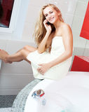 Woman in bathroom speaking on mobile phone. Beautiful woman in bathroom speaking on phone Royalty Free Stock Photography