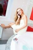 Woman in bathroom speaking on phone. Beautiful woman in bathroom speaking on phone Stock Images