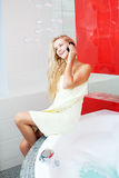 Woman in bathroom speaking on phone. Beautiful woman in bathroom speaking on phone Royalty Free Stock Photos