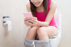 Woman in bathroom. Woman take phone and smile happily in the bathroom Stock Photos