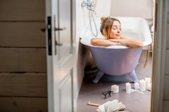 Woman in the bathroom. View through the bathroom door on the beautiful woman relaxing in the retro bathtub royalty free stock photography