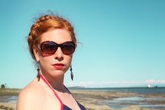 Woman in bathsuit. Serious red hair woman posing on a rock in a swimming suit vintage style Royalty Free Stock Images