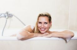 Woman in bathtub. Blond woman sitting in bathtub and smiling Stock Image