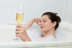 Woman in bathtub drinking champagne Stock Images