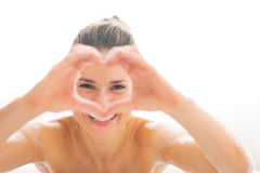 Woman in bathtub looking through heart shaped hand Royalty Free Stock Photos