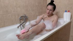 Woman in bathtub with sponge washing feet. In room stock video