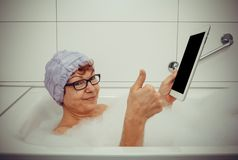 Woman in bathtub with tablet computers make ok. Retro style stock photos