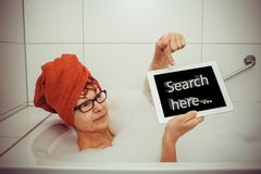 Woman in bathtub with tablet computers, space for text Royalty Free Stock Images