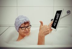 Woman in bathtub with tablet computers take OK, retro style Royalty Free Stock Images