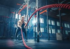 Woman with battle rope battle ropes exercise in the fitness gym. stock photography