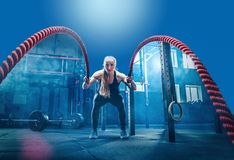 Woman with battle ropes exercise in the fitness gym. royalty free stock images