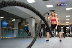 Woman with battle ropes exercise in the fitness gym. Young female wearing sportswear royalty free stock photography