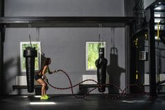Woman with battle ropes exercise in the fitness gym. Young woman training in the dark gym.  Royalty Free Stock Image