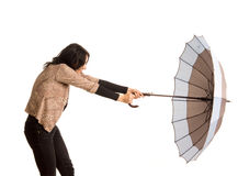 Woman battling with her umbrella Stock Photography