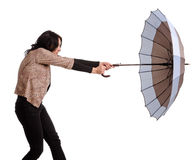 Woman battling with her umbrella Stock Images