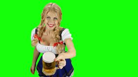 Woman in bavarian costume gives beer and winking eyes. Oktoberfest. Green screen stock video