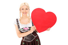 Woman in Bavarian costume holding a red heart Stock Image