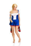 Woman in Bavarian dress holding her shoes. Stock Photos