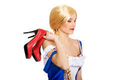 Woman in Bavarian dress holding her shoes. Royalty Free Stock Photo