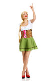 Woman in Bavarian dress pointing up. Royalty Free Stock Photo