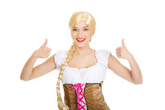 Woman in Bavarian dress with thumbs up. Royalty Free Stock Photos