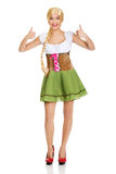 Woman in Bavarian dress with thumbs up. Stock Photo