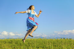 Woman in bavarian traditional dirndl. A woman in bavarian traditional dirndl jumping in the nature stock photo