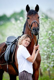 Woman and bay horse in apple garden. Stock Photo