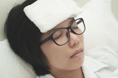 Woman be ill. Sickness and flu of asian woman. Close up of glasses woman be ill with headache resting on her bed royalty free stock image