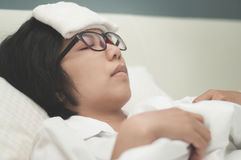 Woman be ill. Sickness and flu of asian woman. Close up of glasses woman be ill with headache resting on her bed Stock Photos