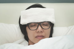 Woman be ill. Sickness and flu of asian woman. Close up of glasses woman be ill with headache resting on her bed royalty free stock images
