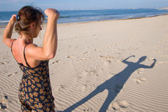 Woman, be strong!. Woman making muscular shadows on beach sand Royalty Free Stock Photo