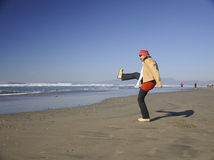 Woman at the beach. Female balancing on one leg at the beach Royalty Free Stock Photo