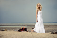 Woman on the beach. A woman wearing a white dress on the beach near a campfire Royalty Free Stock Image