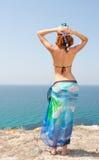 Woman on the beach. Woman in bikini and sarong on the beach looking at the sea Stock Photo