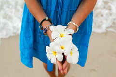 Woman on beach. With tropical flower Plumeria in hand Royalty Free Stock Image