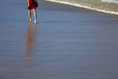 Woman on the Beach. A woman walks on the beach barefoot Royalty Free Stock Images