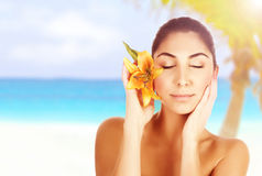 Woman on the beach. Photo of beautiful woman on the beach with yellow lily flower in head, arabic female with closed eyes enjoying dayspa, beauty treatment, body Royalty Free Stock Photography