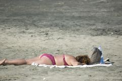 Woman on the beach. Old fat woman in bikini lying on the beach stock photography