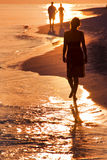 Woman on the beach. Lonesome woman goes for a walk at sundown on the beach Stock Photography
