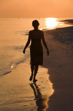 Woman on the beach. Lonesome woman goes for a walk at sundown on the beach Stock Photos