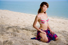 Woman on the beach. Asian woman kneeling and relaxing on the beach Stock Photo