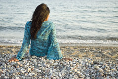 Woman on beach. A rear view of a beautiful asian woman sitting alone on a pebbly beach and looking out to the sea Royalty Free Stock Image